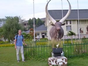 vor dem Ankole-Museum. Dieses Denkmal erinnert an die Bedeutung der Kuh für die Kultur. Konkret erinnert sie an einen Krieg im Jahr 1740, der ausgebrochen ist, nachdem ein König eine besonders schöne Kuh eines anderen Stammes stehlen lassen hat, weil man ihm sie nicht verkaufen wollte. 4000 Tote